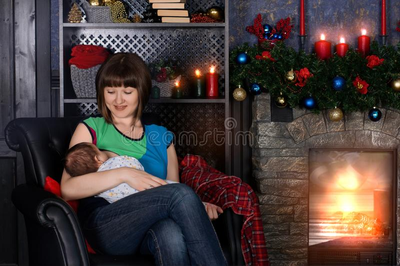 Young mother breastfeeding and looking with love at her baby near fireplace. The wall behind is decorated with Christmas balls stock image