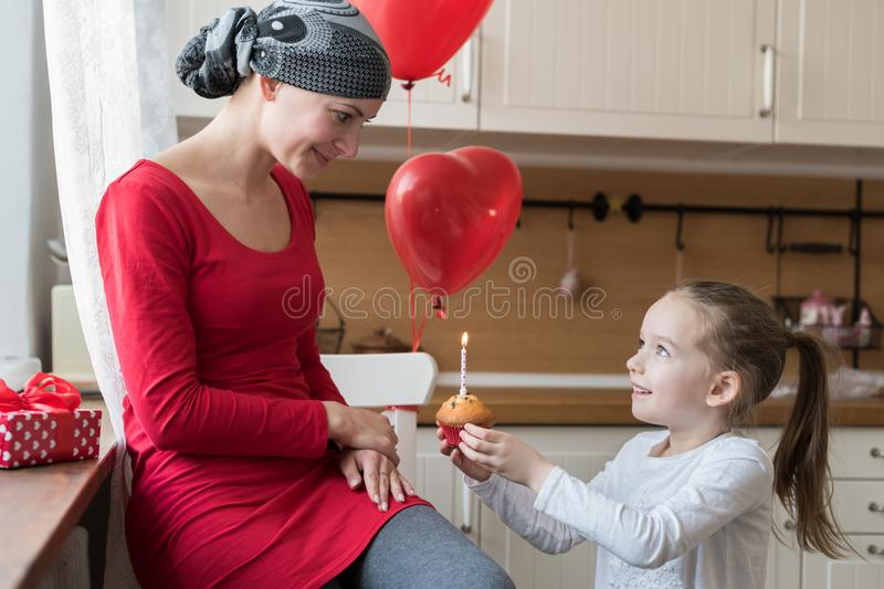 Young mother, cancer patient, and her cute daughter, celebrating birthday with balloons and presents. Lifestyle family support concept stock photo