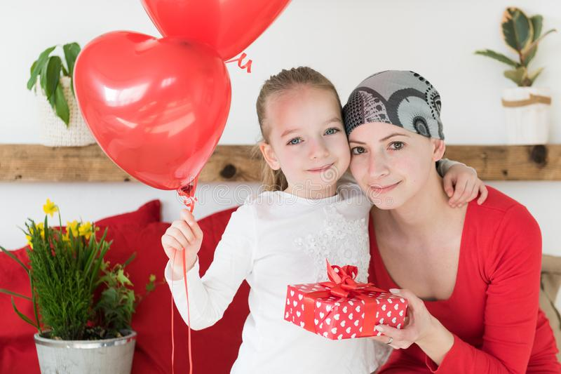Young mother, cancer patient, and her cute daughter, celebrating return home from hospital. Welcome home or birthday party. royalty free stock photography