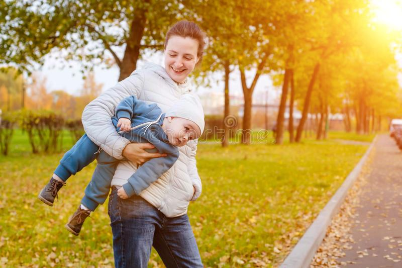 A young mother carries a one year old boy in her arms. Walk with the child in the park at sunny day stock photography