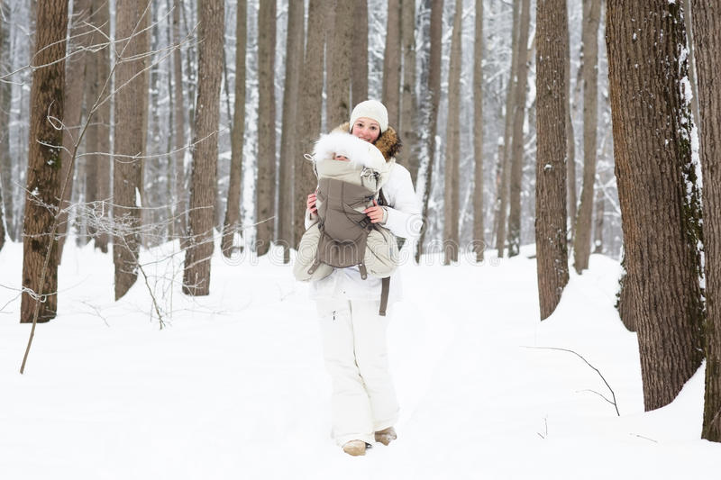Young mother carrying her baby in forest on snowy day stock photos