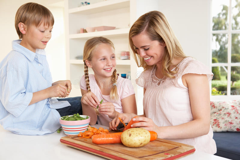 Young mother with children peeling vegetables royalty free stock photo