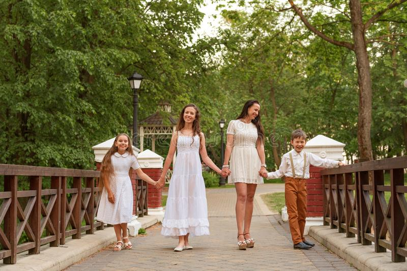 Young mother with children in white dresses walking along the bridge holding hands and laughing smiling. Young mother with children siblings in white dresses stock images