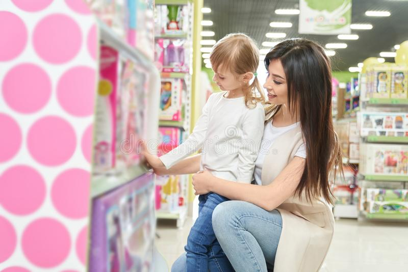 Young mother choosing doll with little daughter in shop royalty free stock photos