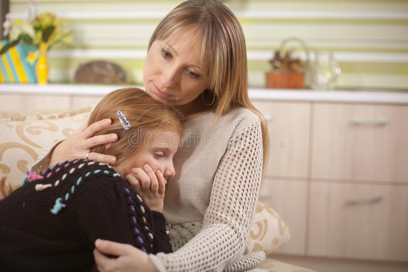 Young mother is comforting her sad daughter stock photo