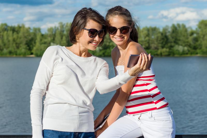 Young mother and a cool teen daughter being photographed and filmed a video in the city park. Friendship between parent and child. stock image