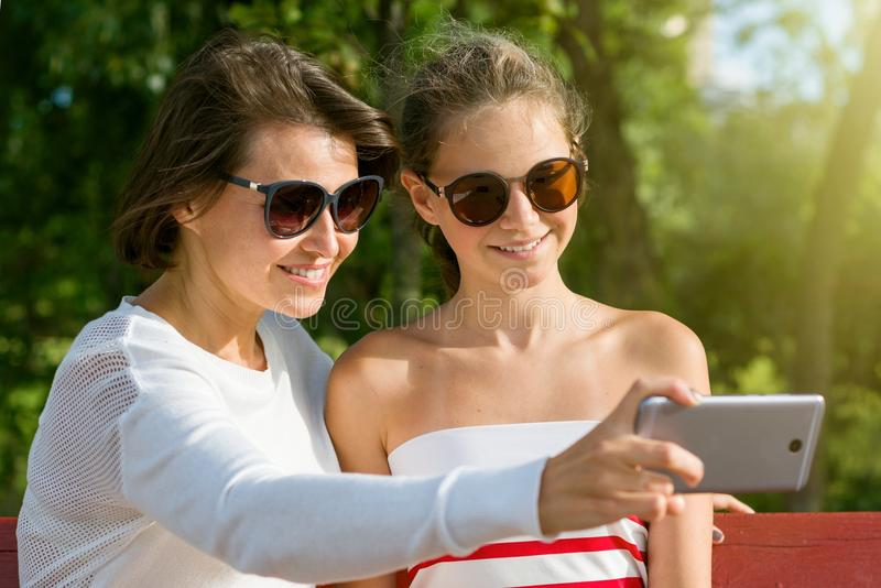 A young mother and a cool teen daughter being photographed royalty free stock photography