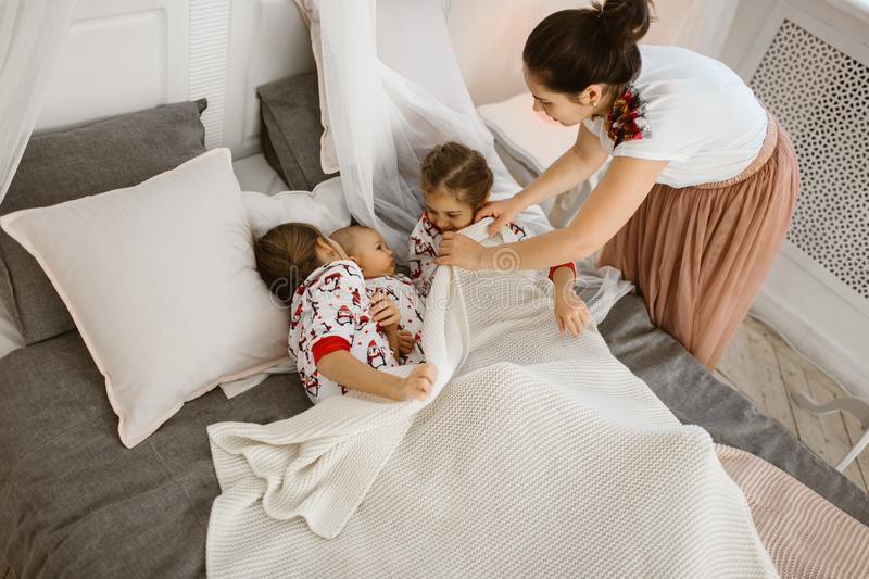 Young mother covers a white blanket for two daughters and a tiny son who lie on the bed  in a light cozy bedroom stock photos
