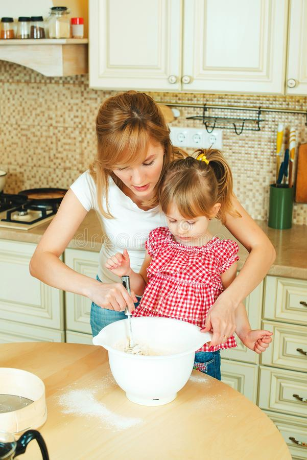 Young mother and cute little daughter preparing the dough, bake cookies and having fun in the kitchen. royalty free stock photo