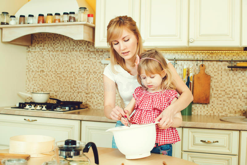 Young mother and cute little daughter preparing the dough, bake cookies and having fun in the kitchen. royalty free stock photography