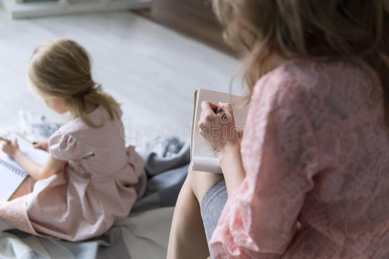Young mother and daughter both blondes sit back and write lists and goals for the new year. Mom writes with her left. Hand. Pink. Natural light. Without a face stock image