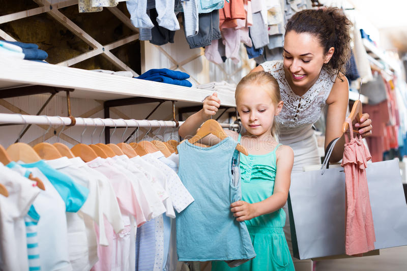 Young mother with daughter buying kids clothes royalty free stock photo