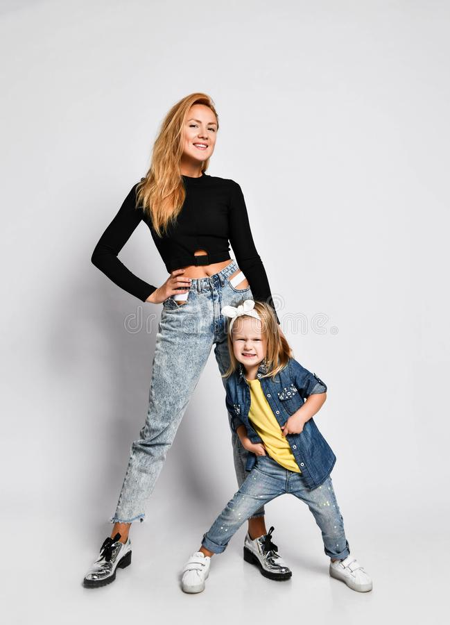 Young mother and daughter in casual jeans wear are cool posing together, smiling, playing. Human relations, family. stock image