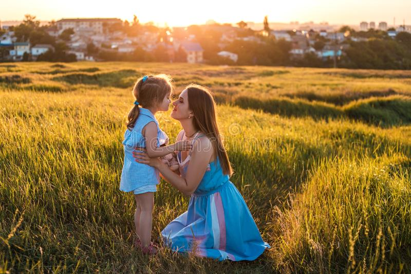 Young mother and daughter, hugging and playing in a golden field of sunshine. stock photos