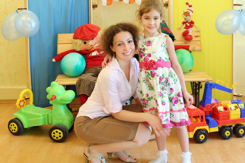 Young mother and daughter in kindergarten royalty free stock photos
