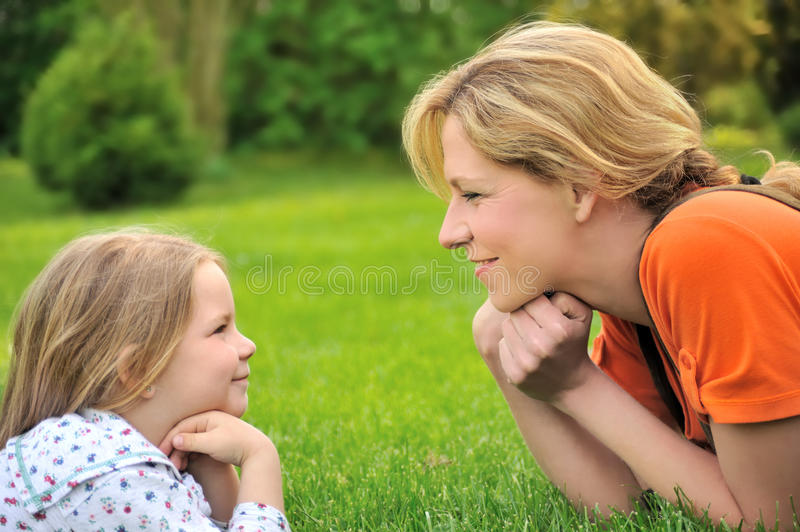 Young mother and daughter laying on the grass stock image