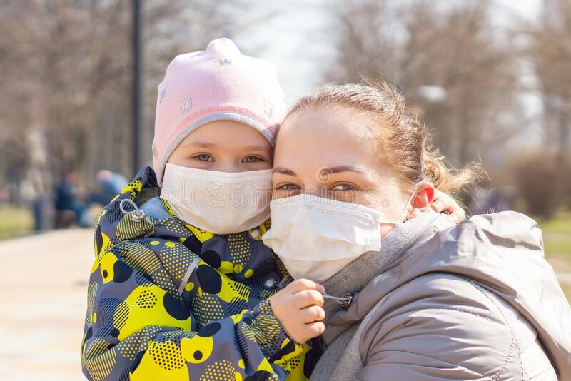 Young mother with daughter in protective masks. Covid-19 Coronavirus Pandemic, Virus Protection.  stock image