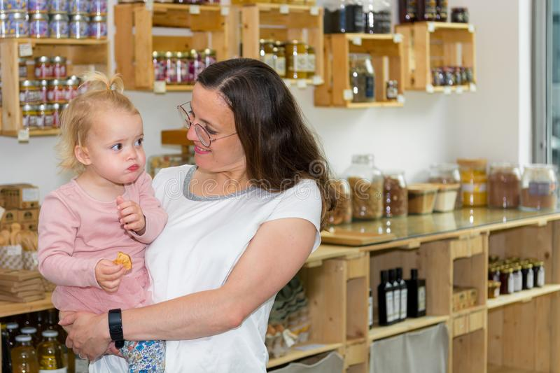 Young mother and daughter shopping in zero waste store. stock photo