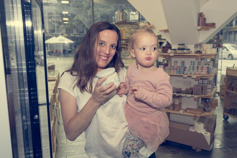 Young mother and daughter shopping in zero waste store. royalty free stock photos