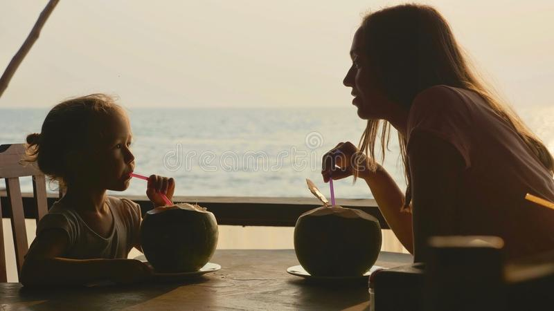 Young mother and daughter sits at seaview cafe and drinks coconuts together. Silhouette of young mother and daughter sits at seaview cafe and drinks coconuts stock image