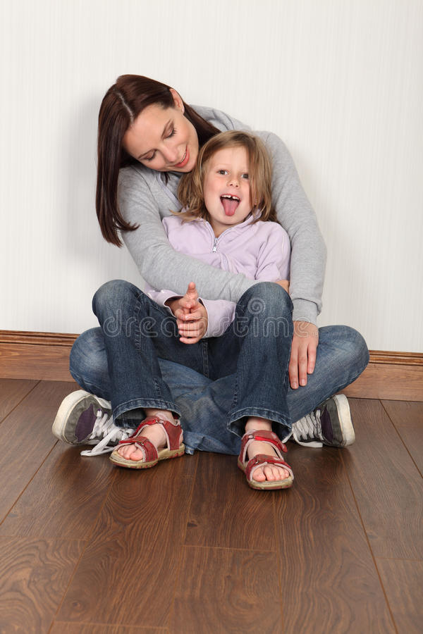Young mother and daughter sitting on floor at home. Happy young family of mum and daughter with hug and embrace sitting on the floor at home. Girl having fun royalty free stock photo