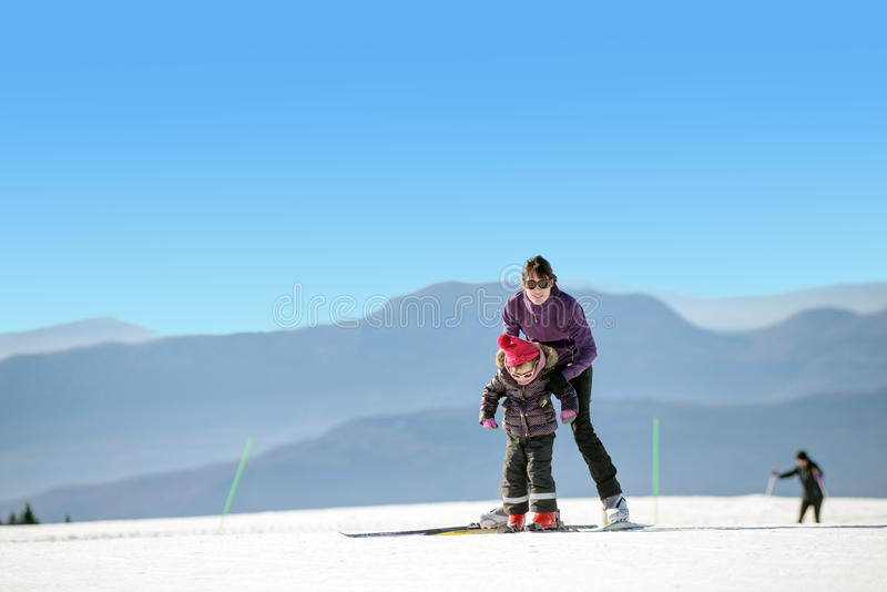 Young mother and daughter on ski vacation royalty free stock images