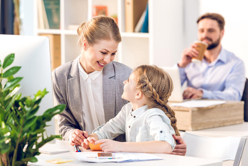 Young mother and daughter talking and hugging in business office stock image
