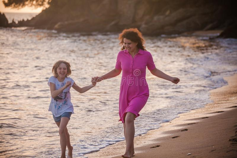 A young mother and a daughter running on Halkidiki beach at sunset, Greece royalty free stock photo
