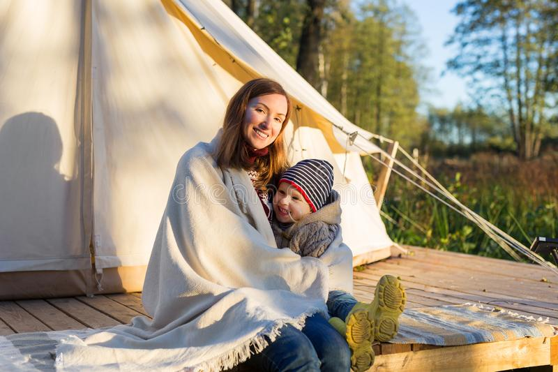Young mother embracing her kid with a blanket while sitting near canvas tent royalty free stock photos