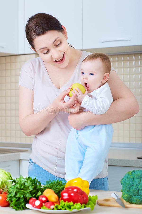 Young mother feeding baby apple. A happy family. stock photos