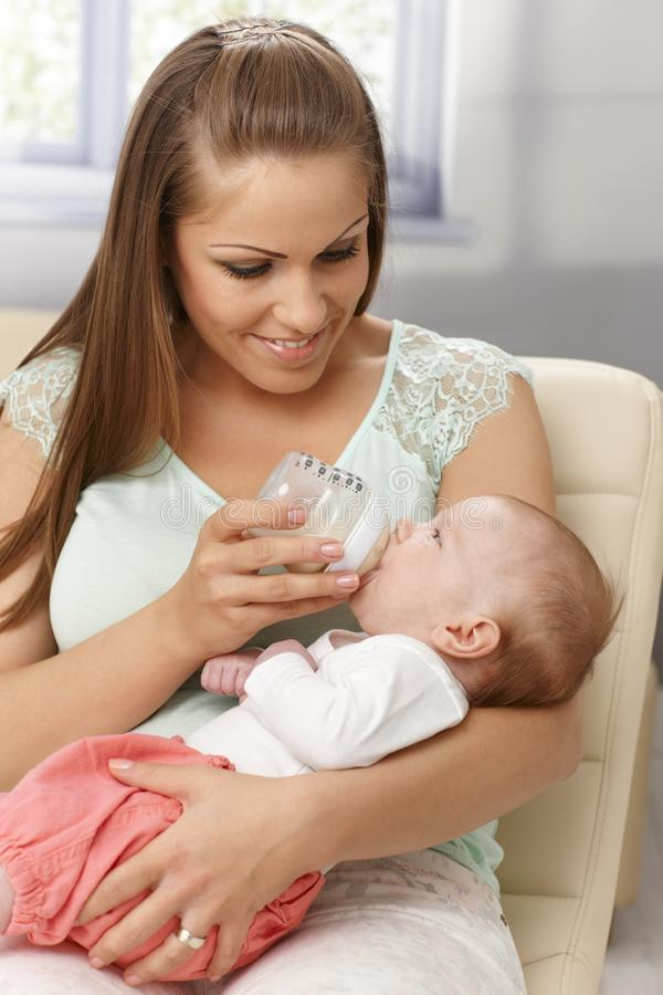 Young mother feeding baby from bottle stock image