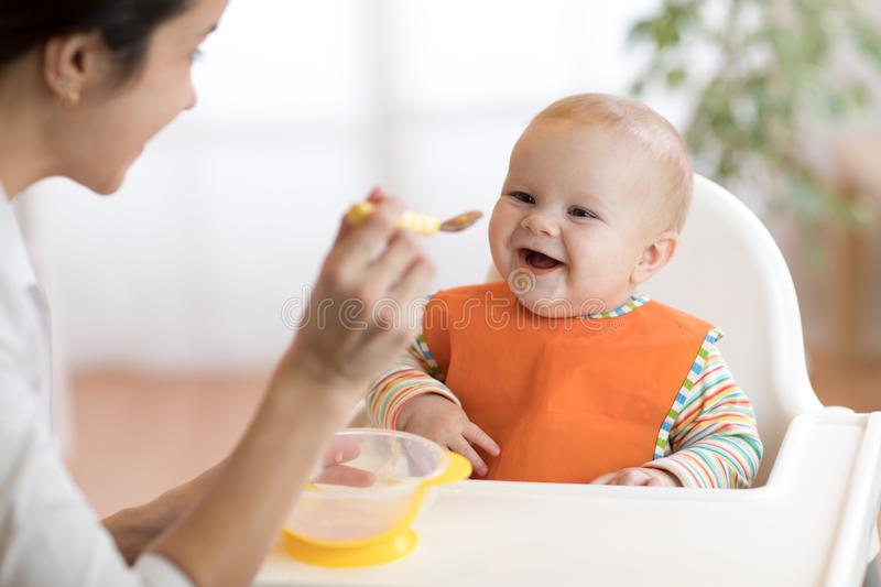 Young mother feeding her baby son with puree royalty free stock photo