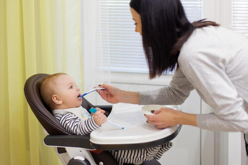 Young mother feeding her little baby son with porridge,who sitting in high baby chair for feeding stock image
