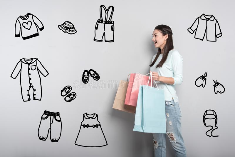 Young mother feeling impressed while buying clothes for her baby stock photos