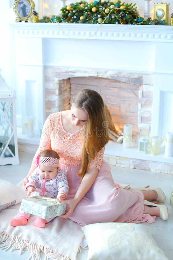 Young mother gifting little daughter present near decorated fireplace. royalty free stock photos