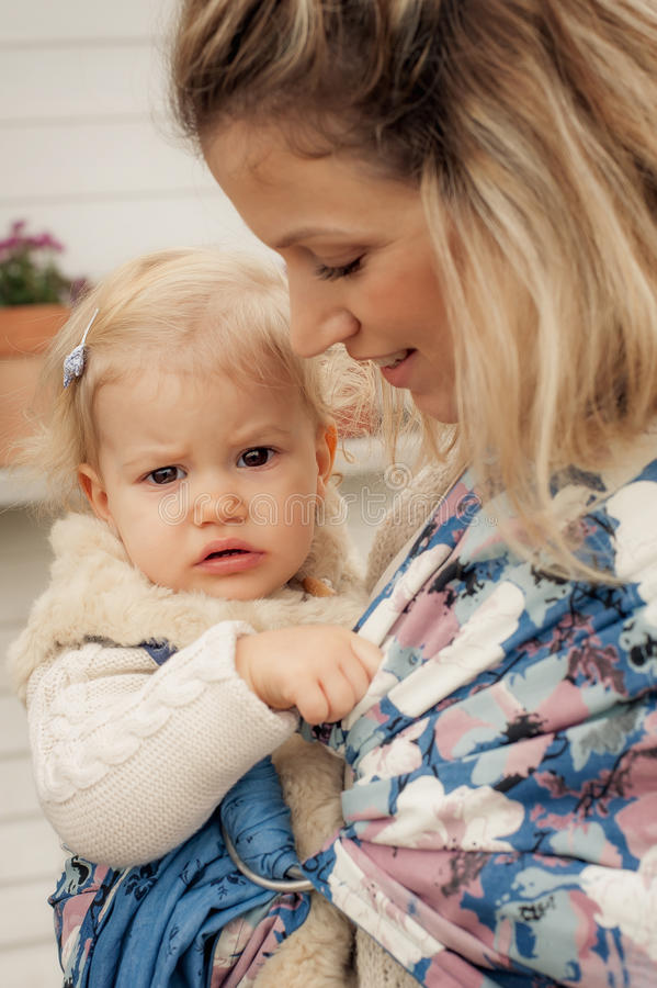 Young mother having her little daughter in baby carrier scarf royalty free stock photo