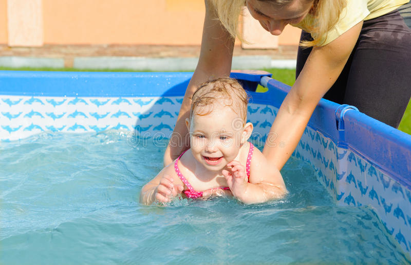 Young mother helping her daughter to swim. In pool stock photography