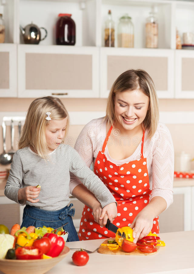 Young mother helping her little daughter to chop stock photo