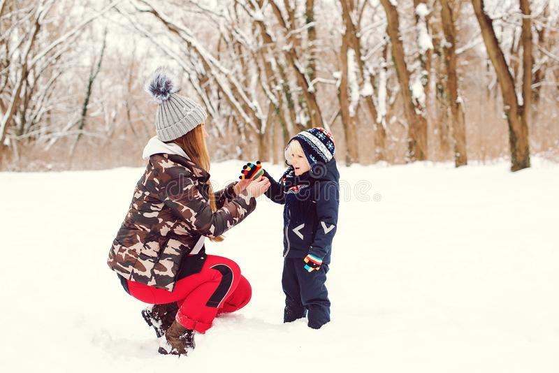 Young mother helping her little son wearing warm gloves outdoors in winter. Happy family during walk at snowy forest. Happy winter stock images