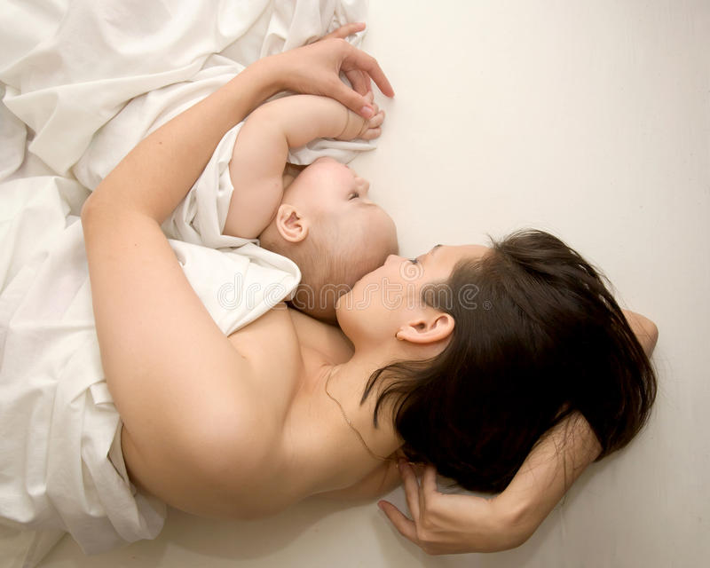 Young mother and her baby sleeping. Lovely young mother and her baby sleeping in bed. A mother's love. The symbol of happiness stock photography