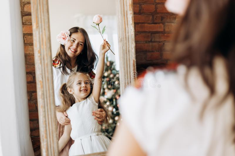 Young mother and her charming little daughter stand in front of the mirror in the room with  New Year`s tree stock photo