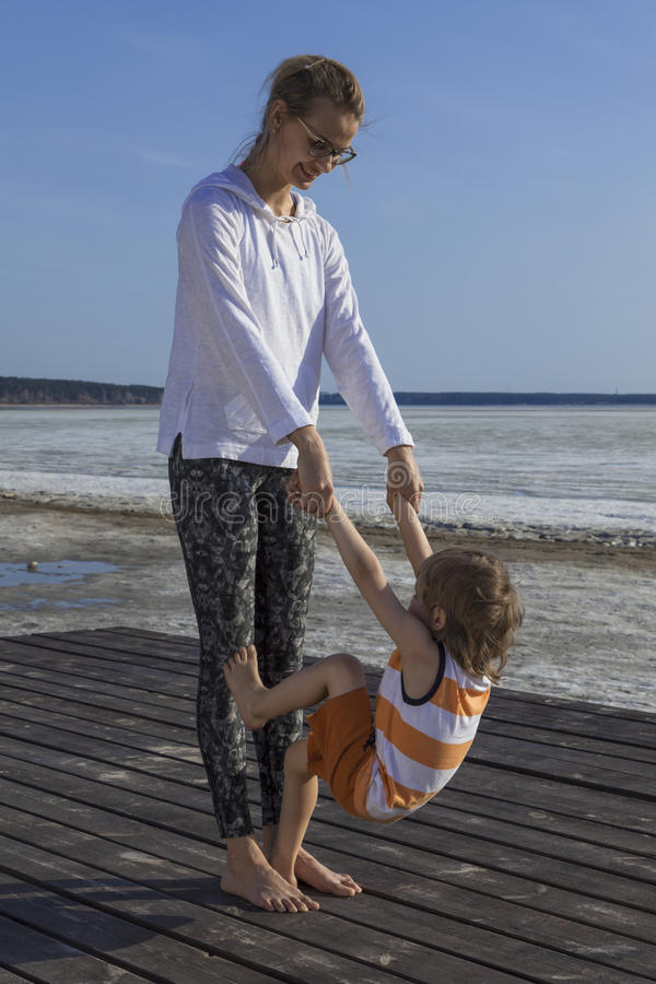Young mother with her child holding hands and doing exerciseon the beach. stock photography
