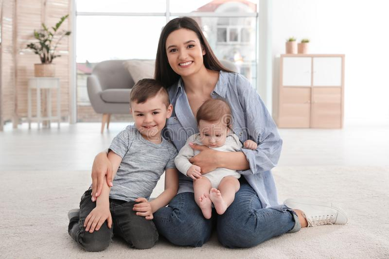 Young mother with her children sitting together on floor stock photography