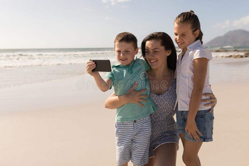 Young mother with her children taking selfie with mobile phone on beach stock image