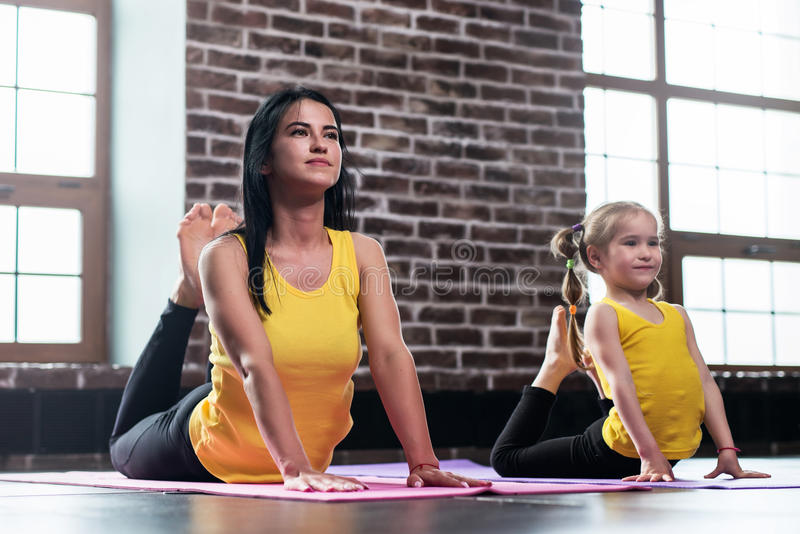 Young mother and her daughter wearing the same sportswear doing king cobra pose during group yoga training royalty free stock images