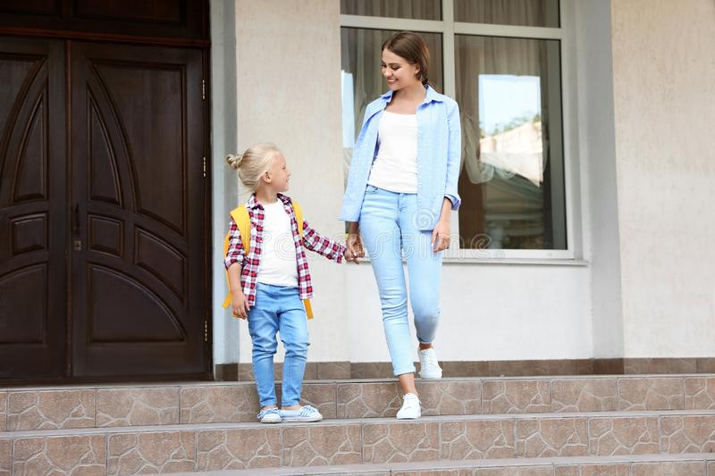 Young mother and her little child with backpack on porch stock photo