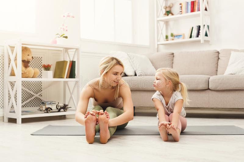 Mother and daughter doing yoga exercises at home stock images