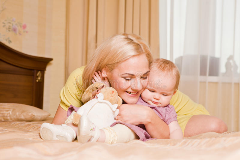 Young mother with her little daughter playing on bed at home royalty free stock photos