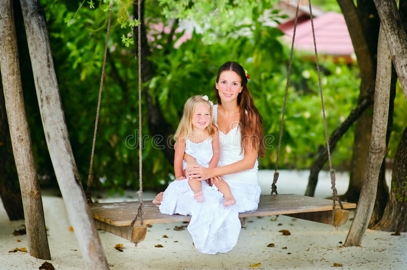 Young mother and her little daughter swinging stock photo