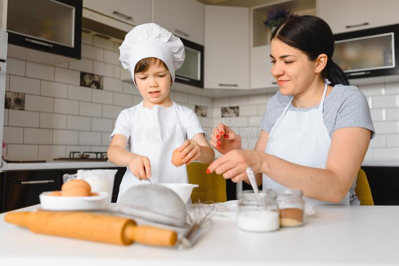 Young mother and her little son baking cookies together at home kitchen.  royalty free stock image